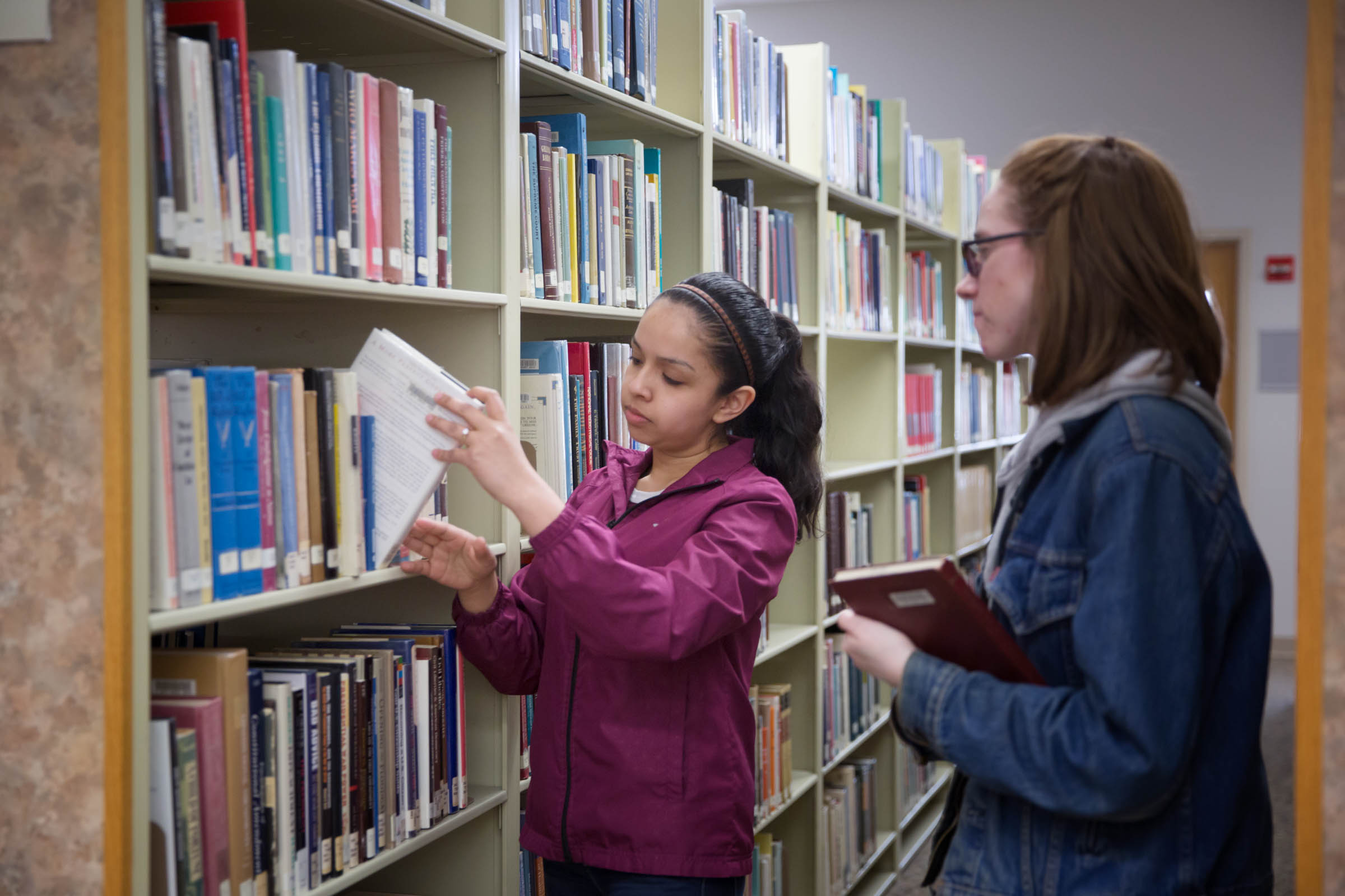 Two students obtaining a book from the library shelves