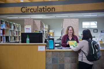 Student checking out an item at Circulation Desk